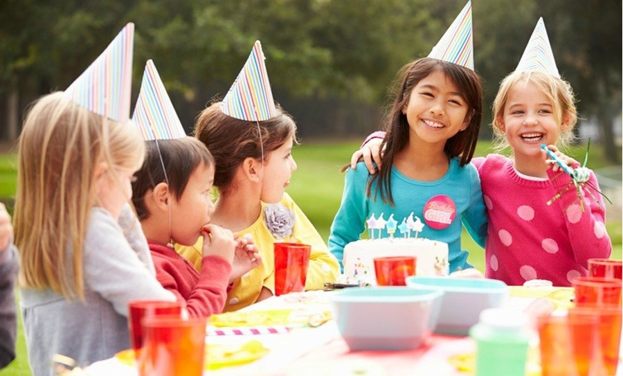 Enfants souriants réunis autour d'un goûter d'anniversaire